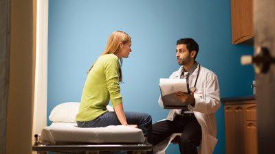 Medico explica paciente sobre a candidíase