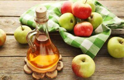 cesta com maças e garrafa de vinagre
