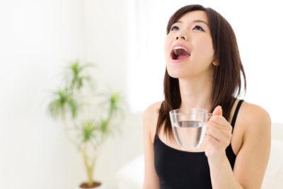 mulher fazendo gargarejo para tratar candidíase oral