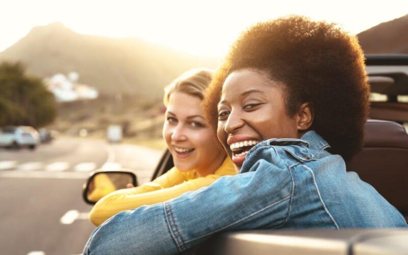 Duas mulheres sorrindo dentro do veículo
